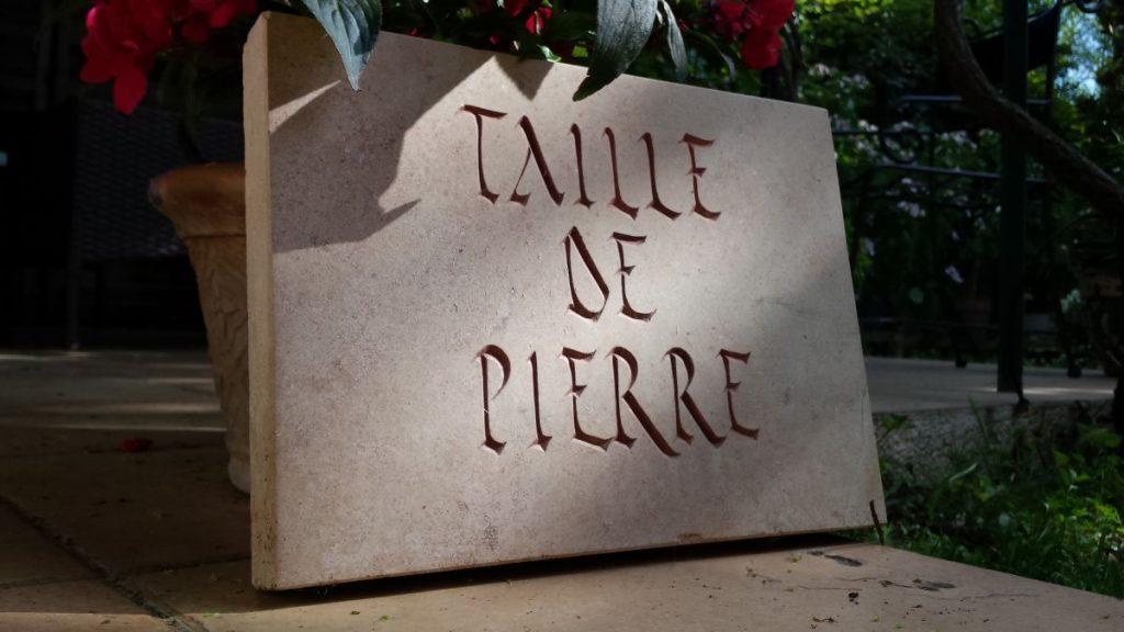 Plaque d'ornement en calcaire oolithique rosé, lettres: calligraphie rustica, peinture rouge marron