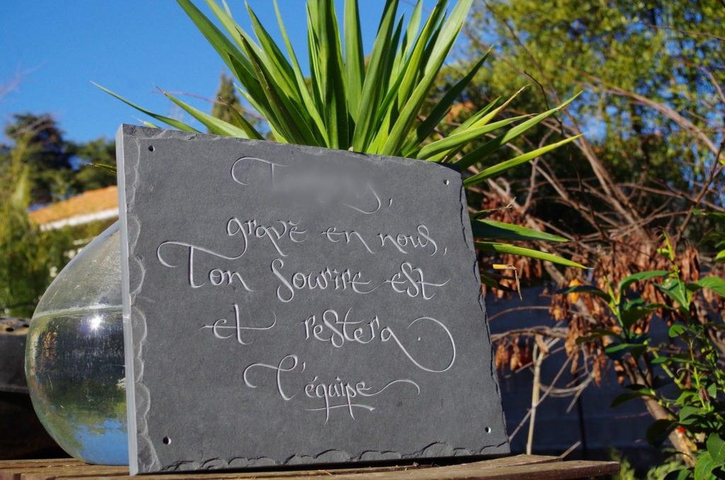 Gravure commémorative sur ardoise ou schiste ardoisier avec arêtes éclatées, lettres brutes sans peinture